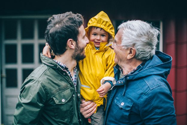Photo of smiling little boy with his father and grandfather